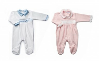 Photograph of blue and pink babygro against a white background